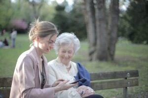 Fille Expliquant La Mère âgée Comment Utiliser Le Smartphone
